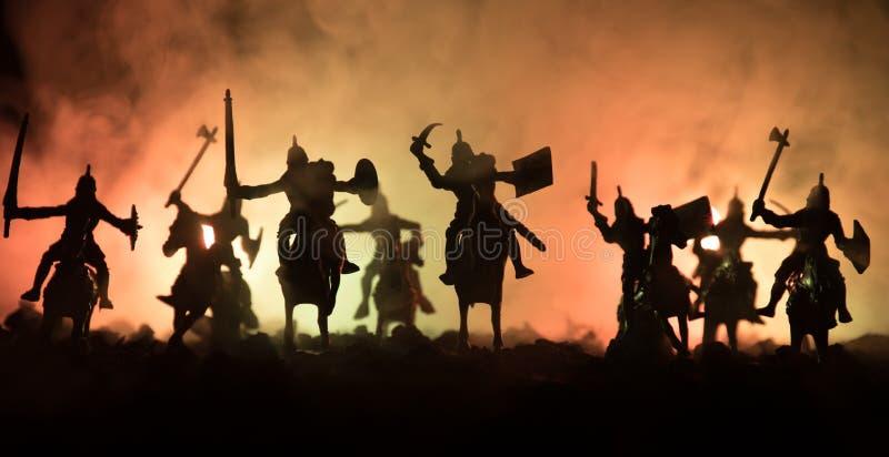 与骑兵和步兵的中世纪战斗场面 图剪影作为分开的对象,在战士之间的战斗被定调子的黑暗的 免版税库存照片