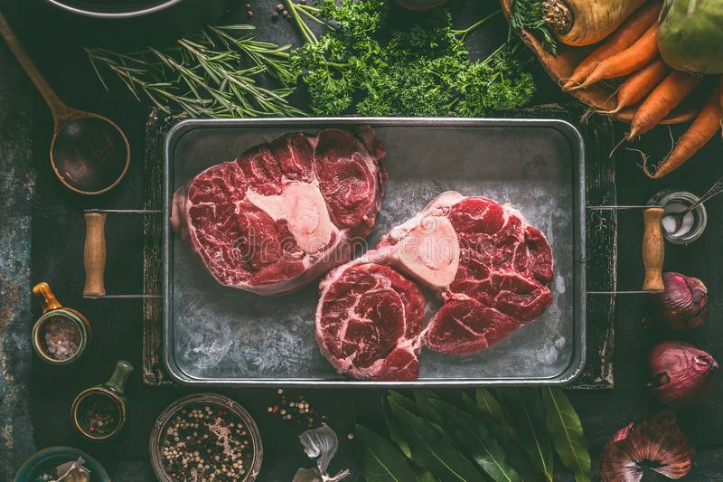 与骨头的未加工的牛肉肉胫骨汤、汤或者炖煮的食物的在金属盘子有成份的鲜美烹调的 库存图片