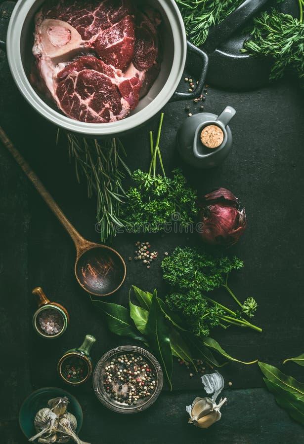 与骨头的生肉在烹调在黑暗的厨房用桌背景用草本和香料汤的,肉骨干或者汤的罐,顶面 免版税库存图片