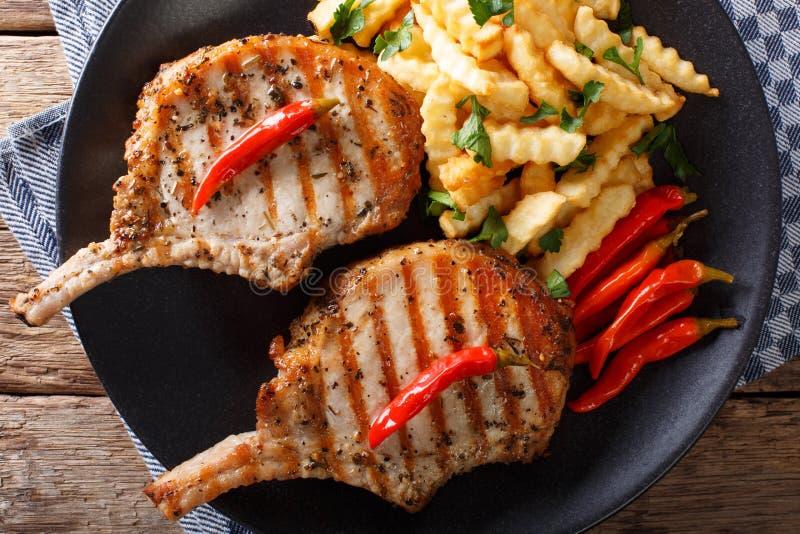 与骨头、辣椒和油炸物特写镜头的烤猪肉在板材 Horiz 库存图片