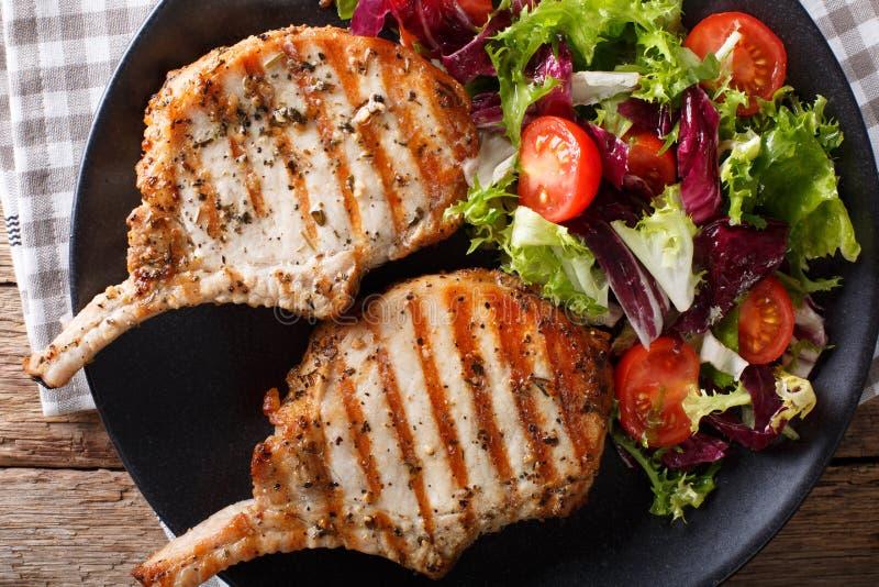 与骨头,新鲜蔬菜沙拉特写镜头的烤猪肉牛排 Ho 图库摄影