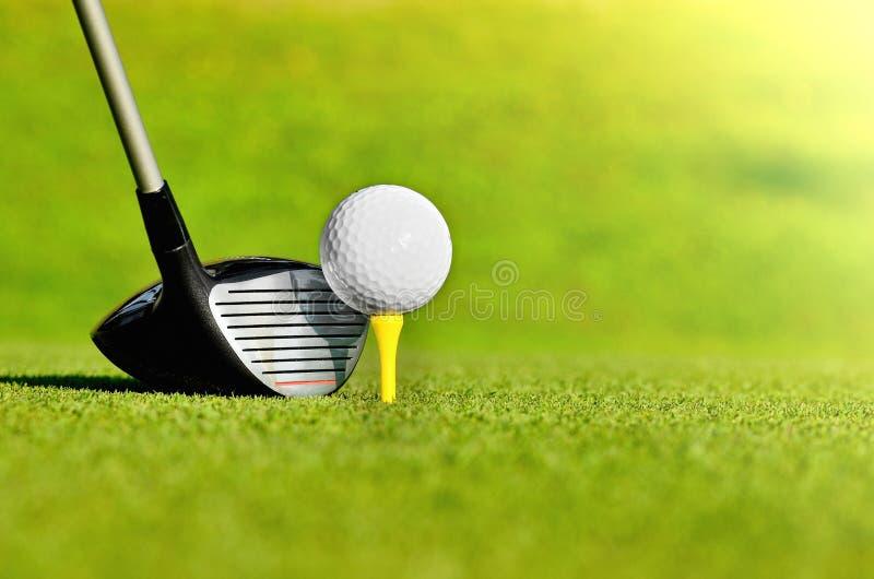 与高尔夫球的司机在发球区域 免版税库存照片