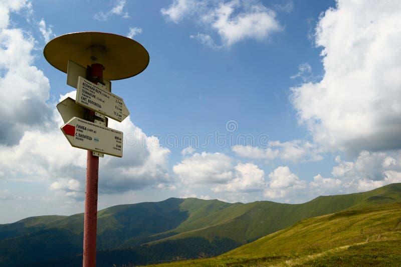 与高峰名字的与足迹方向的路标和箭头在山脉 免版税库存照片
