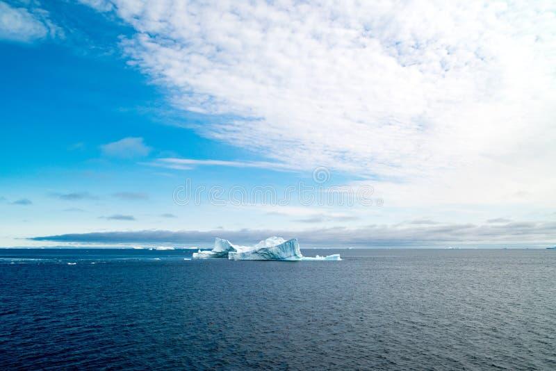 与高积云的格陵兰风景在深蓝北冰洋有冰山的,格陵兰的天空蔚蓝 免版税库存照片