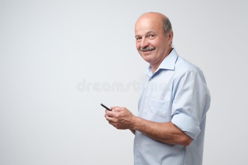 与髭的成熟商人在使用写的电话的蓝色衬衣sms 图库摄影