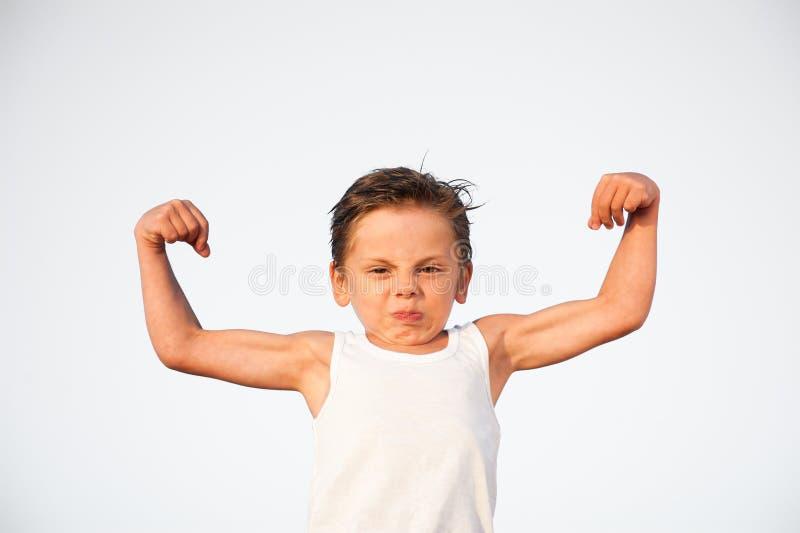 与鬼脸的滑稽的矮小的白种人孩子在他的显示二头肌肌肉的面孔 库存照片