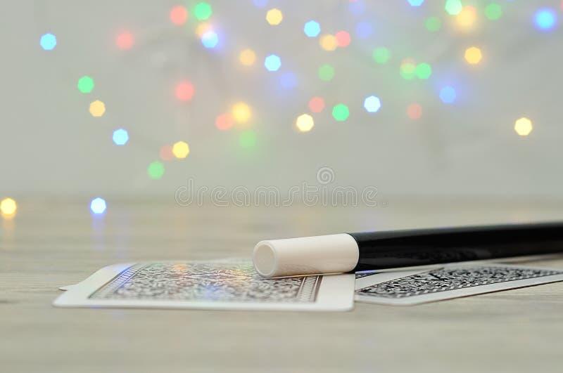 与魔术师鞭子的卡片和出于焦点光背景 免版税库存照片