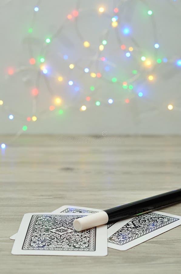 与魔术师鞭子的卡片和出于焦点光背景 免版税库存图片