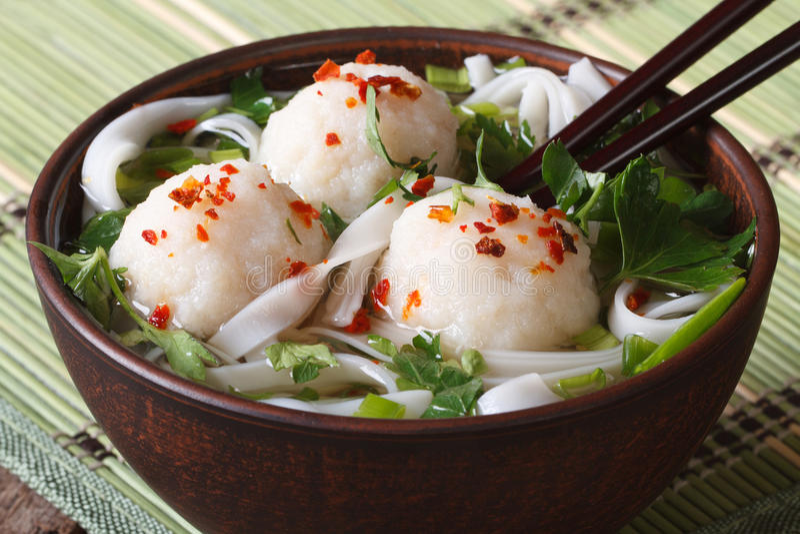 与鱼丸、新鲜的草本和米线关闭u的亚洲汤 免版税库存图片