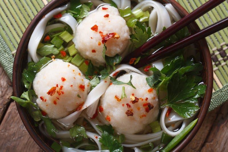 与鱼丸的亚洲汤在碗和筷子顶视图 免版税库存图片
