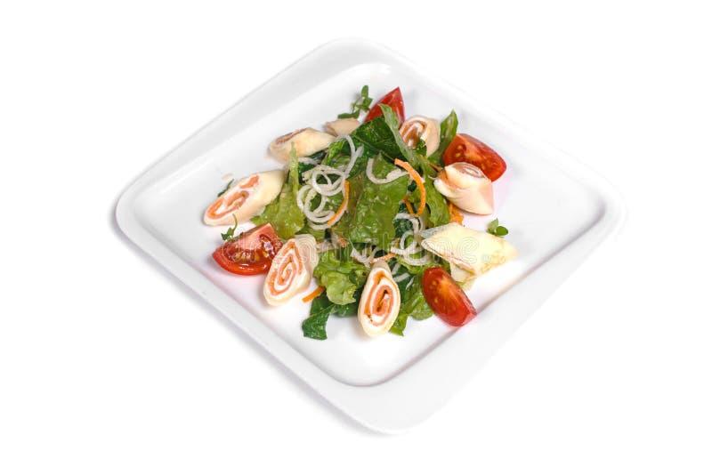 与鱼卷、绿色、葱和蕃茄的沙拉在被隔绝的白色背景的一块白色板材 免版税图库摄影