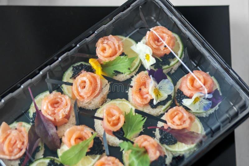与鱼和可食的花的可口开胃菜在饭盒 食物的,餐馆,菜单,承办酒席概念 免版税图库摄影