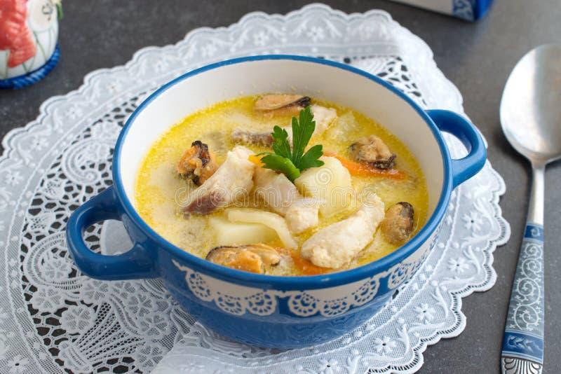 与鱼片和淡菜的乳脂状的汤在一块白色布料的一个蓝色陶瓷罐在灰色抽象背景 健康吃浓缩 免版税库存图片