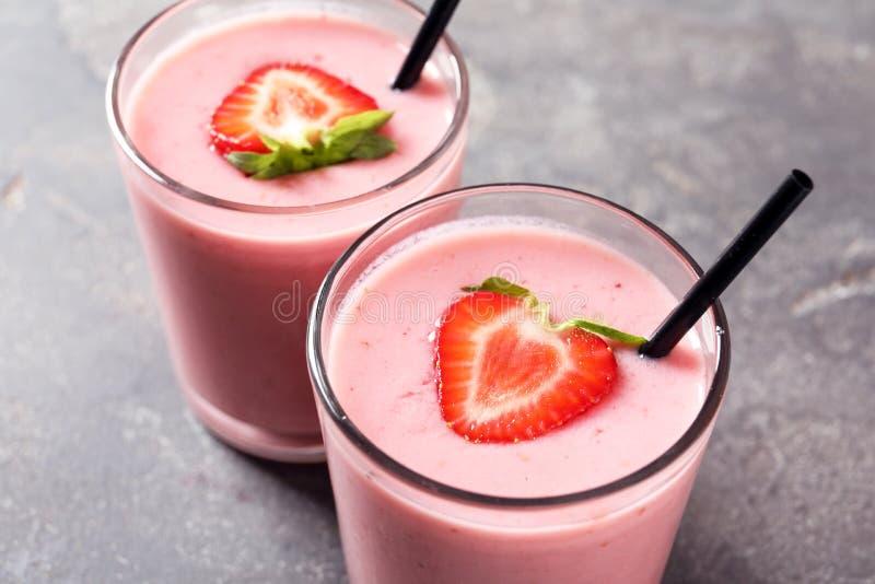 与鲜美草莓圆滑的人的玻璃 库存照片