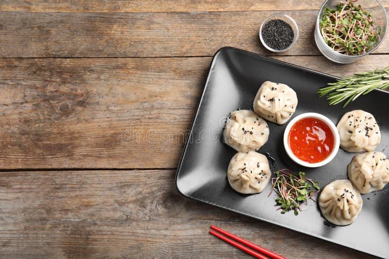 与鲜美baozi饺子、新芽、芝麻和调味汁板材的平的被放置的构成  文本的空间 库存照片