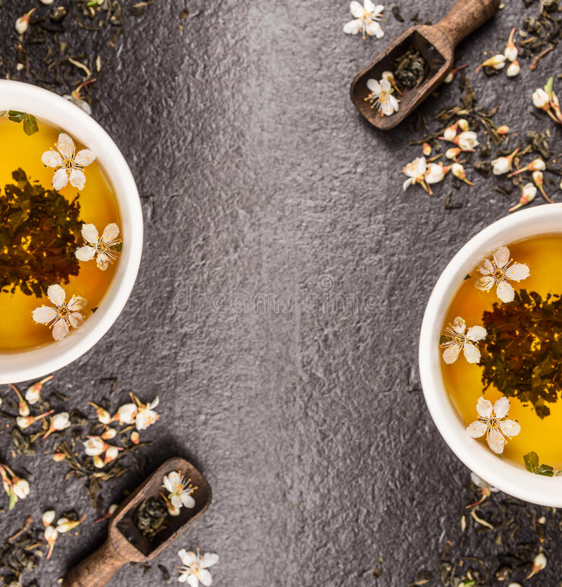 与鲜花和茶杯的绿色茉莉花茶在黑石背景,框架,顶视图 图库摄影
