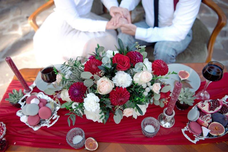 与鲜花的浪漫与夫妇的桌和蜡烛在背景的爱 免版税库存图片