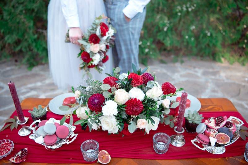 与鲜花的浪漫与夫妇的桌和蜡烛在背景的爱 免版税库存照片