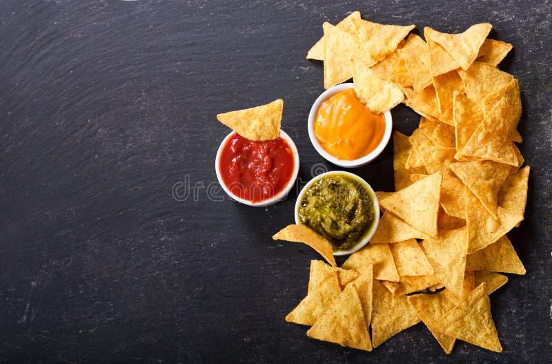 与鳄梨调味酱捣碎的鳄梨酱、辣调味汁和奶酪浓汁的墨西哥烤干酪辣味玉米片玉米片 免版税库存照片