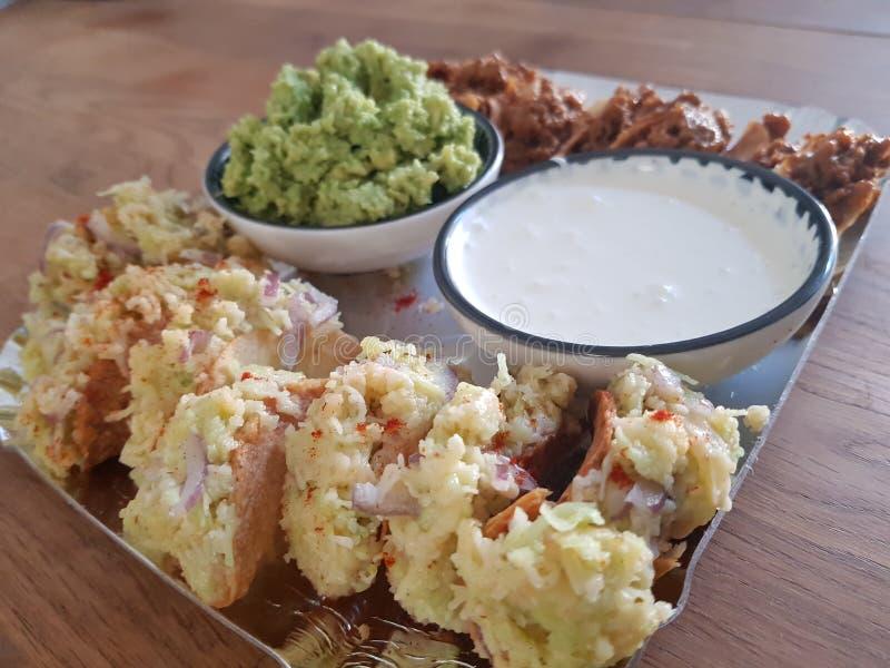 与鳄梨调味酱捣碎的鳄梨酱和奶油freche的微型3块乳酪炸玉米饼 库存图片