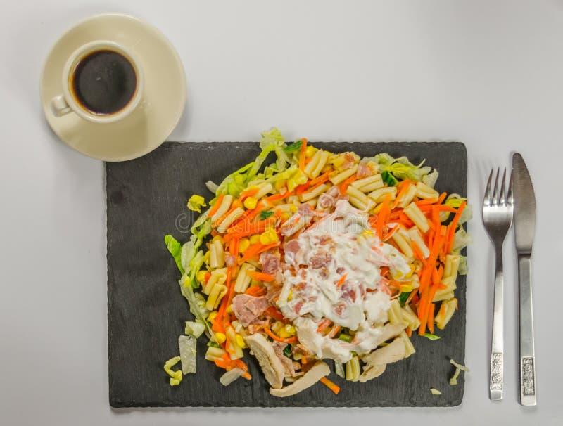 与鸡、烟肉和意大利酱的沙拉注册一块黑石头 库存照片