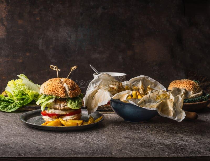 与鸡、莴苣、无盐干酪和蕃茄的自创鲜美汉堡服务用在土气厨房用桌bac的炸薯条土豆 库存照片