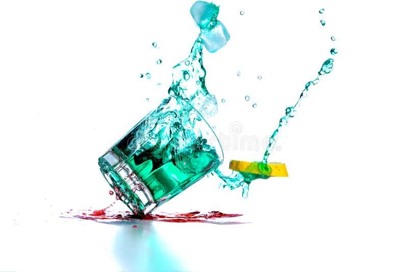 与鸡尾酒下落和溢出的饮料玻璃 免版税库存照片