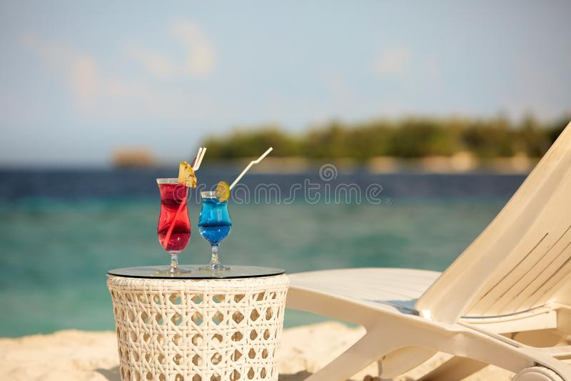 与鸡尾酒的两块玻璃在海滩长凳或轻便折叠躺椅附近的桌与蓝色海洋和在背景的白色沙子上 免版税库存照片