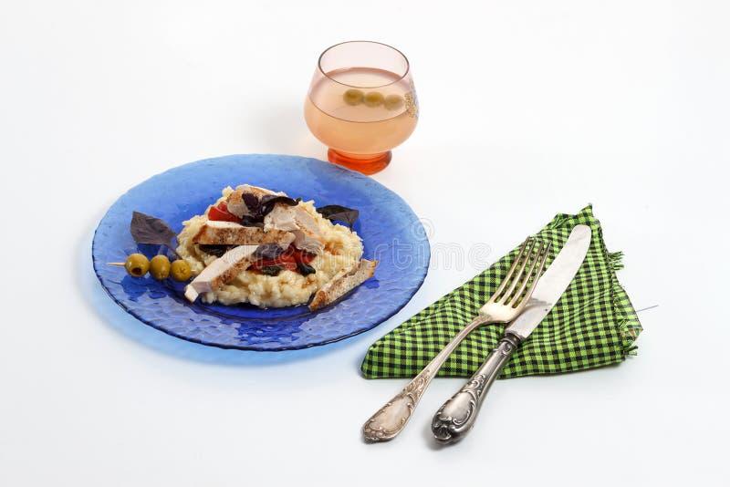 与鸡的传统意大利意大利煨饭、蕃茄、蓬蒿和巴马干酪在蓝色板材有刀子的和叉子和杯酒 免版税库存图片