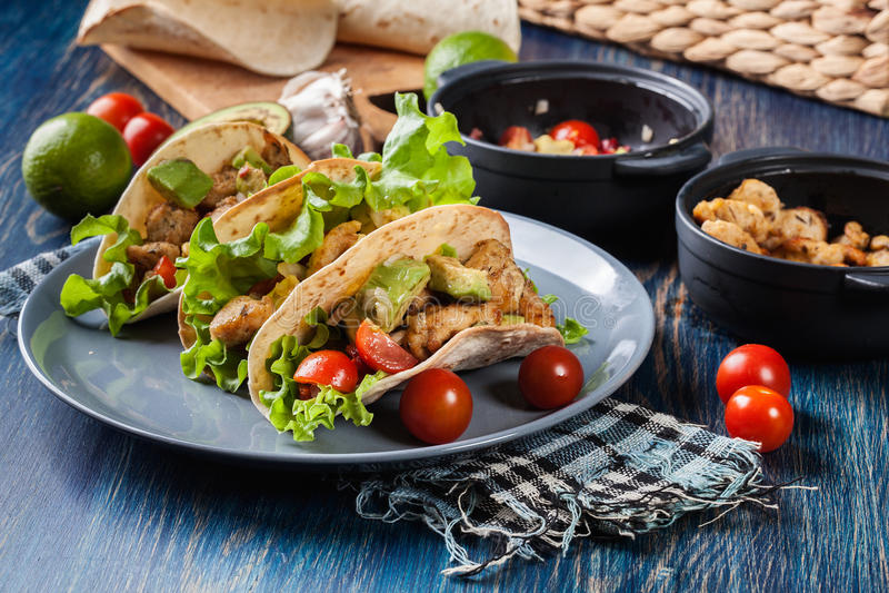 与鸡的地道墨西哥炸玉米饼和辣调味汁用鲕梨、蕃茄和辣椒 库存照片