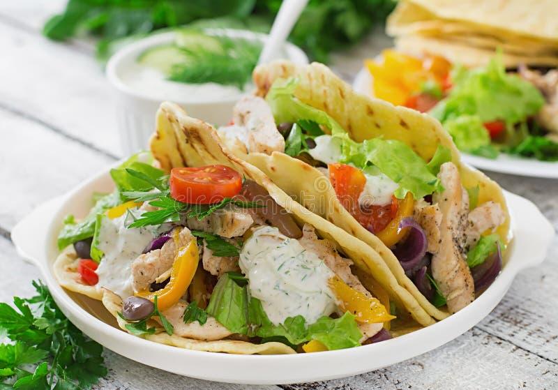 与鸡的墨西哥炸玉米饼、黑豆和新鲜蔬菜和调味汁 免版税库存照片