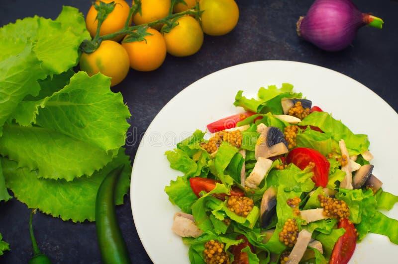 与鸡的新鲜的沙拉,蘑菇、莴苣、蕃茄和芥末浸洗 黑暗的石背景 顶视图 特写镜头 免版税库存照片