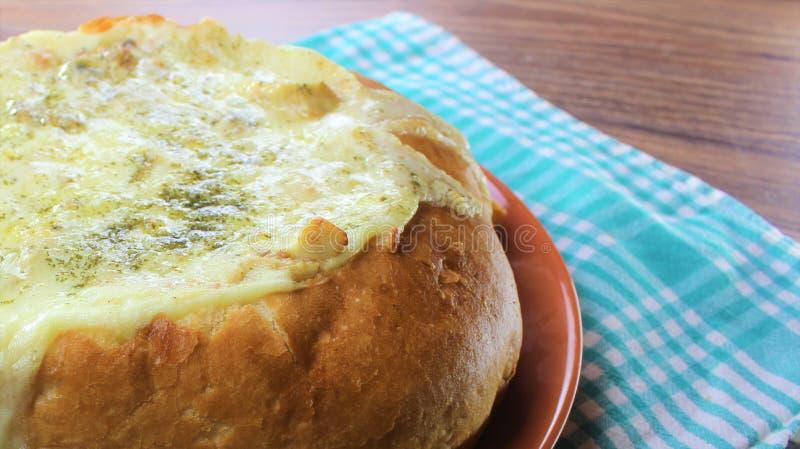 与鸡的被充塞的面包和在橙色板材和红色,棕色背景的熔化乳酪 库存照片