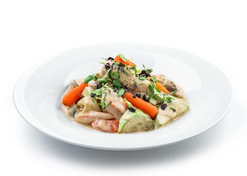 与鸡肉、红萝卜、蘑菇、夏南瓜和在白色背景隔绝的乳酪调味料的热的沙拉 健康食品,顶视图 免版税库存图片