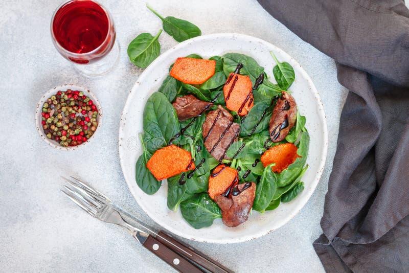 与鸡肝和被烘烤的南瓜的温暖菠菜沙拉用香料和芳香抚人 免版税库存图片