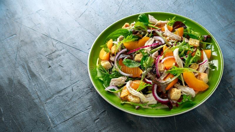 与鸡胸脯、桃子、红洋葱、油煎方型小面包片和菜的新鲜的沙拉在一块绿色板材 健康的食物 免版税库存照片