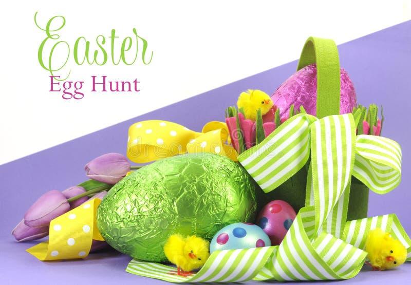 与鸡蛋黄色,绿色丝带和篮子的愉快的复活节明亮的颜色复活节彩蛋狩猎题材  免版税库存照片