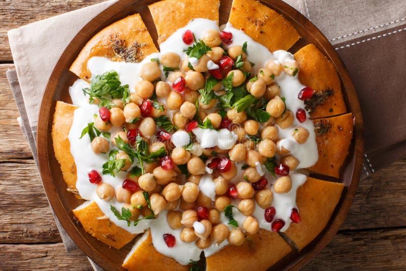 与鸡豆和酸奶传统阿拉伯盘特写镜头的Fatteh皮塔饼在板材 水平的顶视图 免版税库存照片