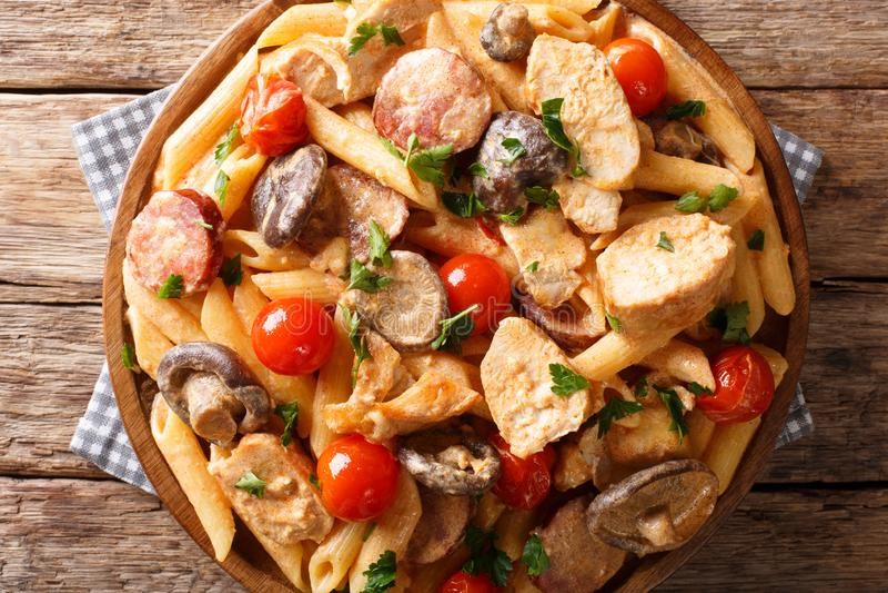 与鸡,蘑菇,熏制的香肠的佩纳面团,盖用奶油奶酪在桌上的调味汁特写镜头 水平的顶视图 库存照片