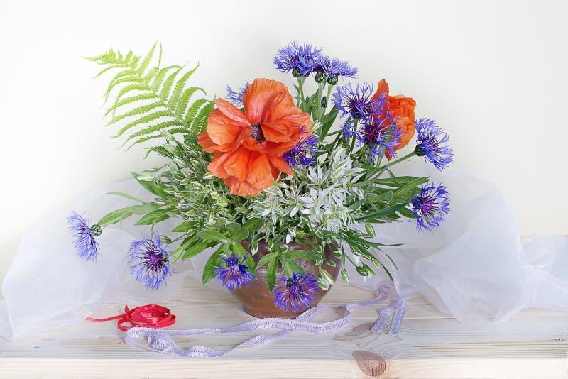 与鸦片,矢车菊,在一个花瓶的snowdrops的花束在白色背景 免版税库存图片