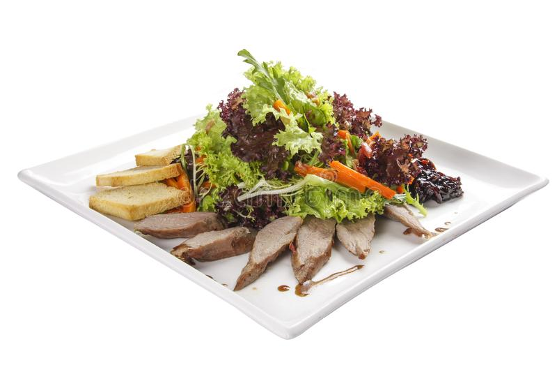 与鸭胸脯的沙拉在一块白色板材 免版税库存照片