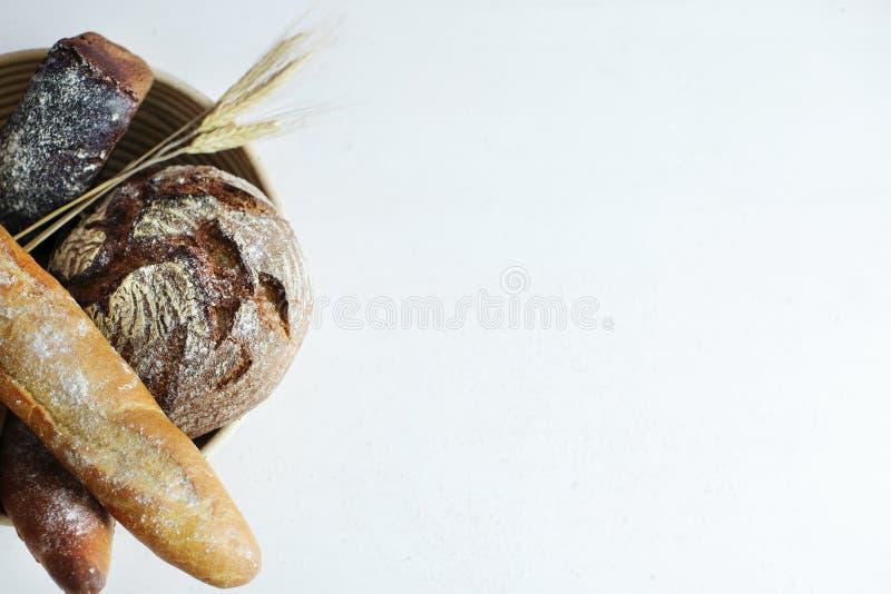 与麦子在面粉的面包店桌上和您的文本的一个地方的耳朵的家制面包 免版税库存照片
