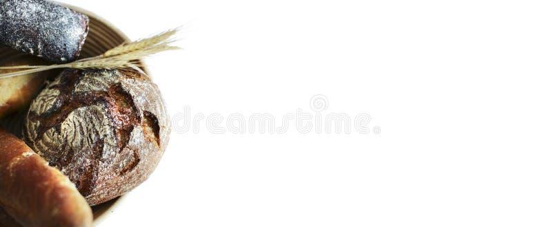 与麦子的耳朵的家制面包在面粉的面包店桌上 查出的空白背景 台式视图 图库摄影