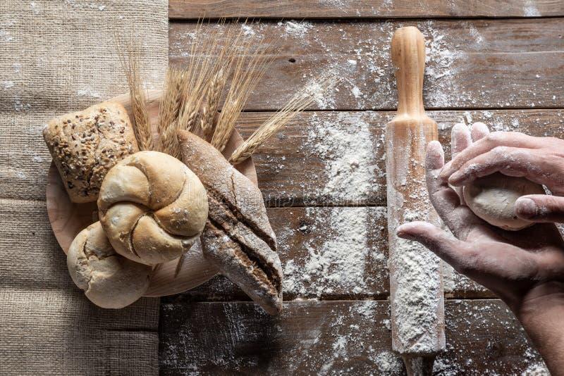 与麦子耳朵和面粉的面包在木板,顶视图 免版税库存图片
