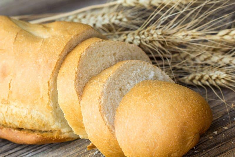 与麦子钉的切的面包在木桌特写镜头 免版税库存图片