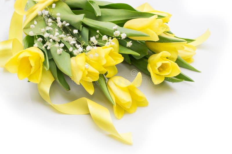 与黄色丝带的黄色郁金香在米黄背景 免版税库存照片