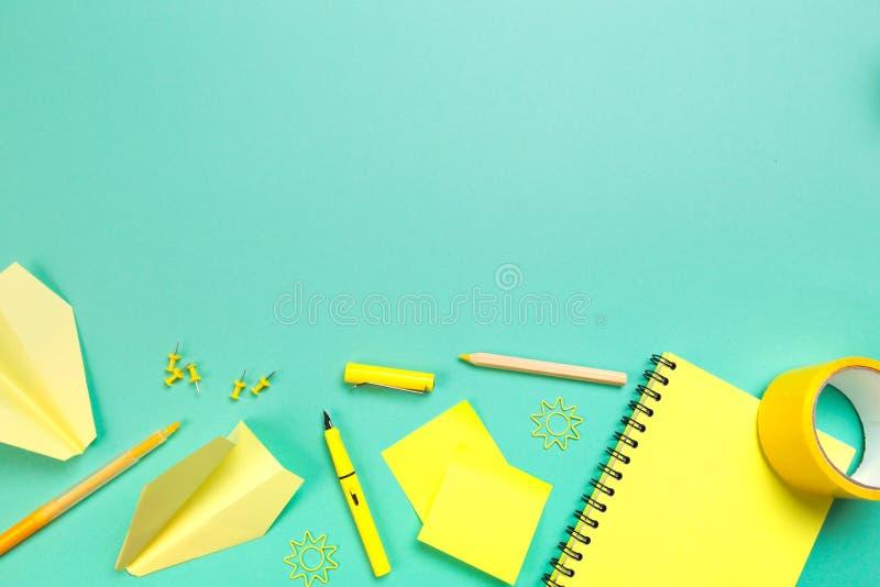 与黄色供应的创造性,时兴,minimalistic,学校或者办公室工作区在深蓝背景 r 库存照片