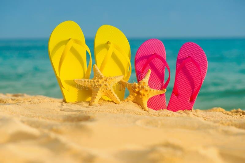与黄色和桃红色凉鞋的海星在沙子站立以海为背景 免版税库存图片