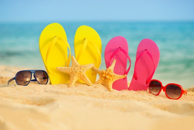 与黄色和桃红色凉鞋的玻璃在沙子站立以海为背景 库存图片