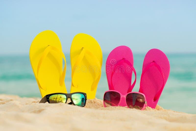 与黄色和桃红色凉鞋的玻璃在沙子站立以海为背景 库存照片